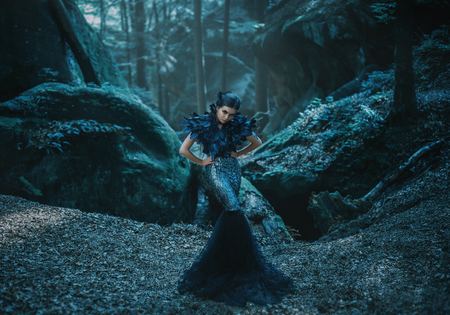 Girl - black raven wanders in the mountains. Gothic photosession theme of Halloween. Unusual, creative outfit