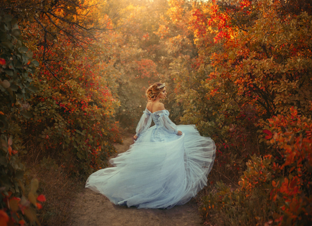 A young princess turns in a beautiful blue dress. The background is bright, golden autumn nature. Artistic Photography