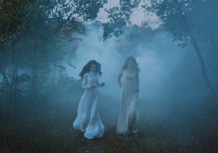 Dense evening fog and silhouettes of running, frightened girls in vintage dresses. Artistic Photography