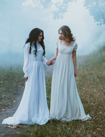 Two frightened girls in vintage dresses, holding hands tightly, wandering in thick fog. Artistic Photography Stock Photo