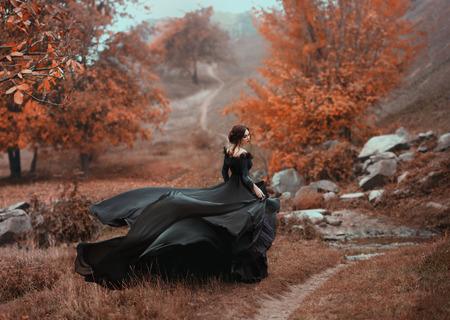 Niesamowita oszałamiająca dziewczyna w czarnej sukni. Tło jest fantastyczne jesienią. Fotografia artystyczna.