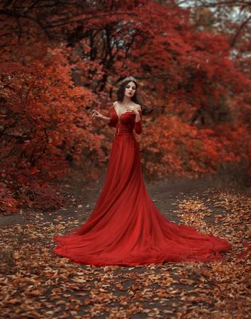 Incrível garota deslumbrante com um vestido vermelho. O fundo é um outono fantástico. Fotografia artística.