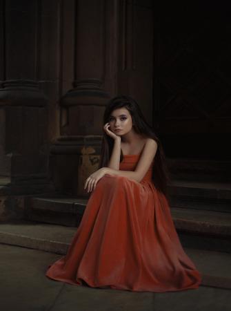 Beautiful brunette girl, with very long hair, in an orange, vintage dress Фото со стока
