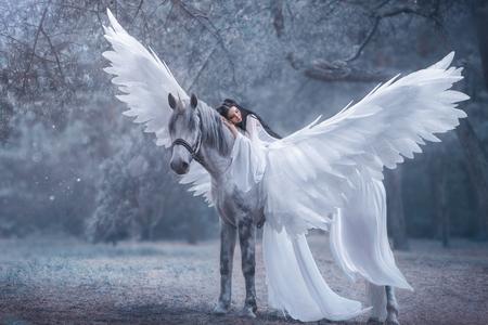 Belo, jovem elfo, andando com um unicórnio. Ela está usando um incrível vestido branco claro. A menina encontra-se no cavalo. Bela adormecida. Fotografia Artística Foto de archivo