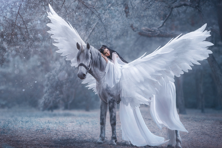 Schöner junger Elf, der mit einem Einhorn spazieren geht. Sie trägt ein unglaublich leichtes, weißes Kleid. Das Mädchen liegt auf dem Pferd. Schlafende Schönheit. Künstlerische Fotografie Standard-Bild