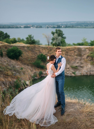 Wedding day. The bride and groom tenderly embrace each other against the backdrop of wildlife at sunset. Stock Photo