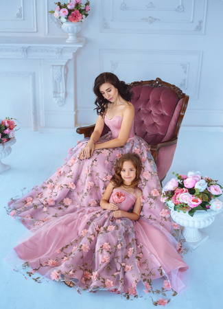 Mom and daughter in luxurious, pink dresses with sakura flowers on a skirt. Family clothes, identical dresses. The background is beautiful, expensive, white, classic interior. Artistic, family photo