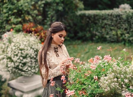 Una ragazza cammina in un giardino fiorito, ha una camicetta vintage con fiocco, i capelli lunghi castani. si prende delicatamente cura dei suoi fiori. Giardiniere innamorato. Fotografia artistica. Amore per le piante