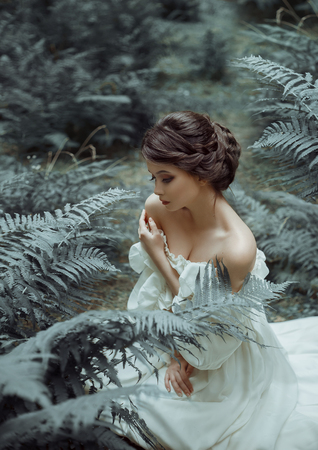The princess sits on the ground in the forest, among the fern and moss. On the lady is a white vintage dress with a deep cutout, beautifully emphasizes a chest. Art photography. Emotions of melancholy