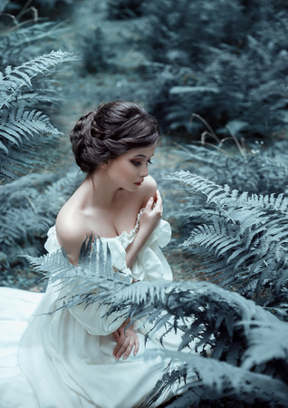 The princess sits on the ground in the forest, among the fern and moss. An unusual face. On the lady is a white vintage dress. Artistic photography. Emotions of melancholy and depression. Cold toning