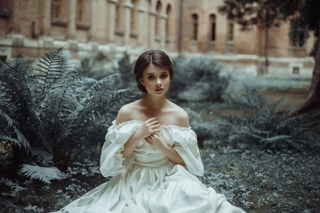An incredibly beautiful princess sits in the castle garden amid the fern and moss. A beautiful, frightened face. Big sad eyes. Collected hair - a neat hair. On the lady - an old ivory dress. Art photo