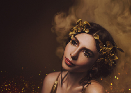 Close-up portrait. Girl with creative make-up and with golden eyelashes. The Greek goddess in a laurel wreath with flowers and handmade roses. Art Photo Stockfoto