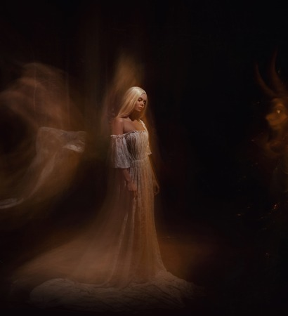 A beauty and a monster of darkness. Ariadne and the Minotaur. The girl is blonde, like a ghost, in a white vintage dress, a gothic, artistic photo bearing emotions of despair and sadness.