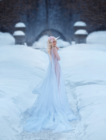 A wonderful creature, a unicorn girl in a light, white, slightly transparent dress, walks through the snow. The background is a frosty winter. Artistic Photography