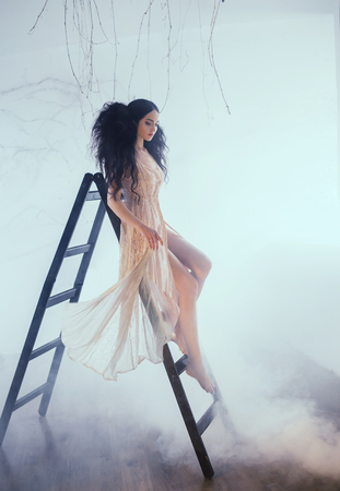 Fairy-tale princess in a peach vintage dress. A girl with an unusual, voluminous hairstyle for long hair with a strong fleece poses on a wooden staircase, in a white room bathed in light and smoke.