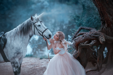 A fairy in a tender vintage dress hugs a unicorn. Fantastic magical, radiant horse. Background river and forest. Blonde girl with wavy hair - light elf. Artistic Photo