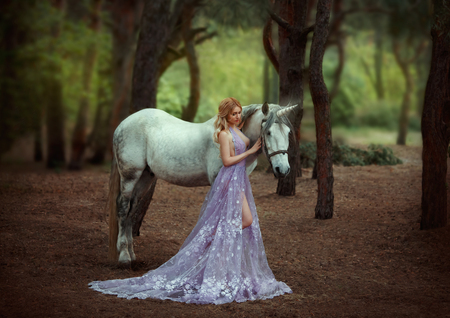 A fairy in a purple, transparent dress with a long train - caught a unicorn. Fantastic magical, radiant horse. Blonde girl walking with pegasus in the forest. Artistic Photography. Stok Fotoğraf