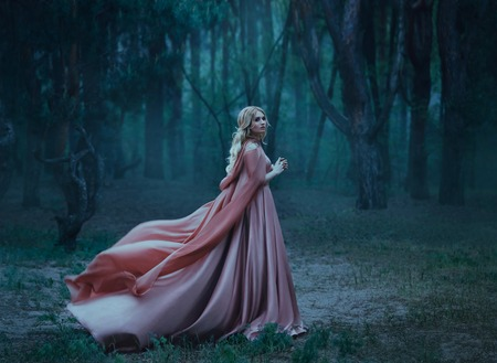 A mysterious blonde girl in a long pink dress with a train and a raincoat that flutters in the wind. The wizard leaves in a forest covered with fog. A background of trees with a haze away. Art photo