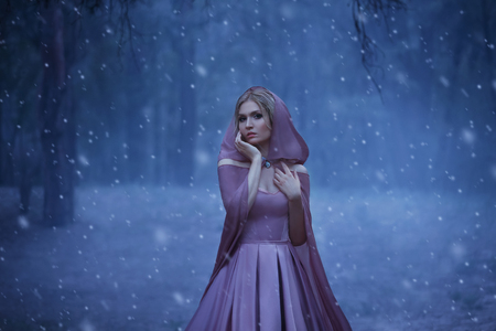 The blonde girl, a bright elf, walks in a gloomy forest covered with fog. Its cold, the snow breaks. The princess in a purple dress and in a cloak with a hood. Art photo in blue shades
