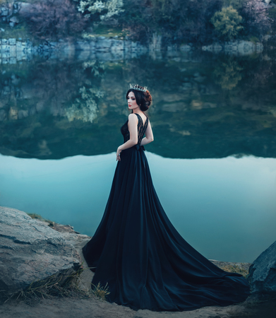 A majestic lady, a dark queen, stands on the background of a river and rocks, in a long black dress. The brunette girl in the gothic crown. Gloomy tone, artistic retouching
