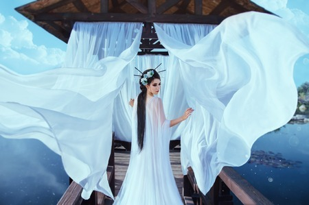 A beautiful sorceress stands on the background of a wooden gazebo by the water, with a white air dress. In the picture there are many flying curtains and silk fabrics. Japanese hairstyle Stock Photo