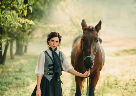 A young lady in a vintage dress strolls through the forest with her horse. The girl has a white blouse, a jabot, a tie, a gray vest, a black long skirt with a train. An ancient, collected hairstyle