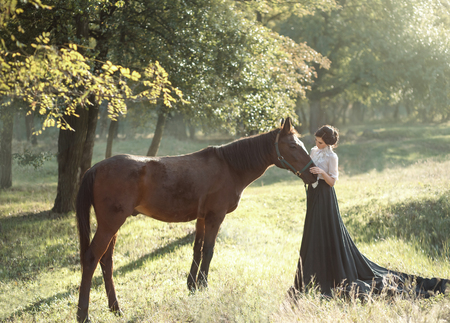 A young lady in a vintage dresses with a long train, lovingly embraces her horse with tenderness and affection. An ancient, collected hairstyle, a gentle make-up. Background of summer fields