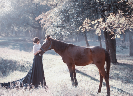 A young princess in a vintage dress with a long train, with tenderness and love, hugs her horse. The brunette girl in a white blouse, black skirt. The background is fantastically beautiful forest Foto de archivo