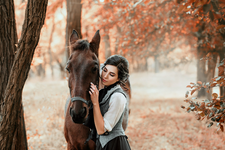 A young lady in a vintage dress, with tenderness and with affection hugs her horse. An ancient, collected hairstyle, a gentle make-up. Gold autumn background. Art photo