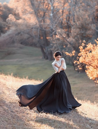 The lady in a vintage dress strolls along the picturesque, golden, autumn hills at sunset. A long train of black skirt fluttering in the wind. The girl is hugging herself from the cold. Art Photo