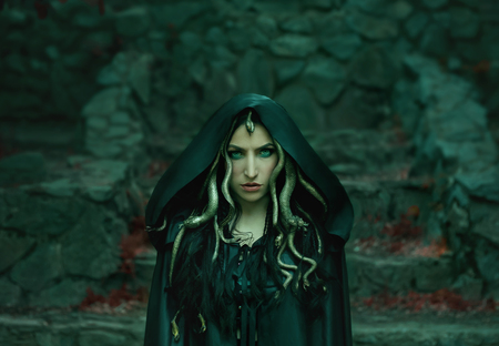 Image of Gorgon Medusa, braid hair and gold snakes, close-up portrait. Gothic make-up in green shades. Background of wild stones. Long black claws and a predatory look. Stok Fotoğraf