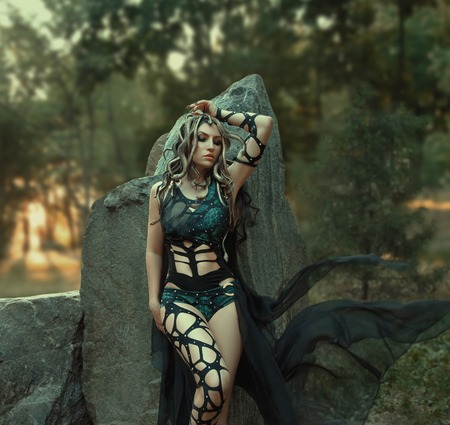Image of Gorgon Medusa, braid hair and gold snakes, close-up portrait. Gothic make-up in green shades. Background of wild stones. Long black claws and a predatory look. Stockfoto