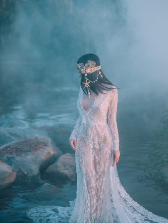 Nymph, walks in the river which was tightened by a thick, impenetrable fog. She has a white vintage, lacy dress. Feast of Ivan Kupala. The girl turned her face away from the camera