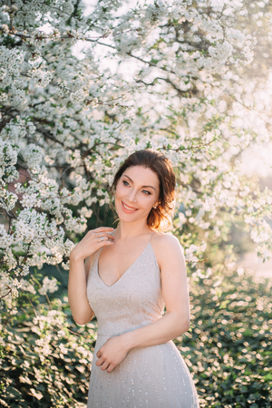 Red-haired girl in a modest, gray dress in rustic style. Portrait of the bride on the background of a blossoming tree with a minimal retouch. A neat, collected hairdo in an airy beam. Nude makeup.