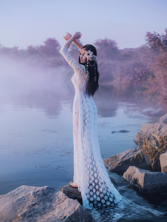 A river nymph in a white lace dress stands on a rock by the lake. The princess has a beautiful wreath with seashells. The background is a fabulous dawn and an early mist over the river