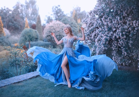Blonde, with a beautiful elegant hairdo, walks in a fabulous blooming garden. Princess in a long gray-blue dress with a long train that flutters in the wind, revealing beautiful, slender legs
