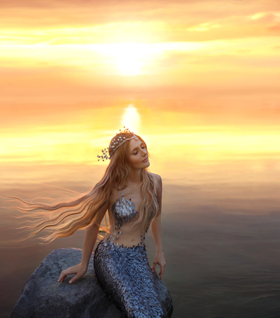 an amazing golden-haired mermaid on the stone in the evening lights of sun Foto de archivo
