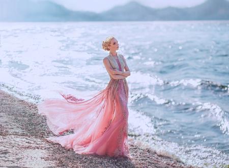 Ein himmlischer Engel in einem fabelhaften Kleid mit weißen Flügeln geht vor der Kulisse von Klippen und Fluss, sonnendurchflutet. Wunderschönes, unglaublich schönes Mädchen mit langen schwarzen Haaren. Kunstfoto