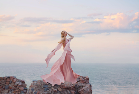 elegant girl elf with blond fair wavy hair with tiara on it, wearing a long light pink rose rozy fluttering dress, standing on the high tower of the old castle. feel free near the blue sea. pastel art Stock Photo