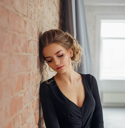 A young blonde girl in a strict, discreet, modest, elegant, long black dress. Delicate natural make-up. Beautiful, elegant, high hairstyle for an average length of hair, with weaving. Evening image