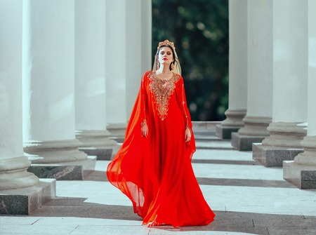 Gorgeous proud dark-haired confident haseki queen roksolana in amazing expensive luxury red long flying dress with gold, beads and precious stones, wearing crown and earrings. art fantasy photo