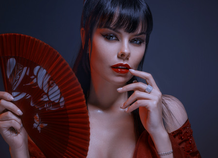 attractive sexy girl with dark black hair, gray eyes, amazing makeup with red lips looks playfully at the camera. wearing a maroon light, loose dress with open shoulders, holds a fan Stok Fotoğraf - 110343830
