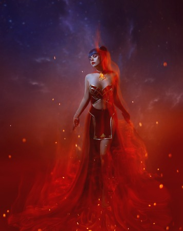 a fire warrior stands in a flame, a gorgeous young slim girl with blue long hair, dressed in an oriental skirt and red top, an open belly and shoulders, decorated with a necklace with a fiery stone Фото со стока