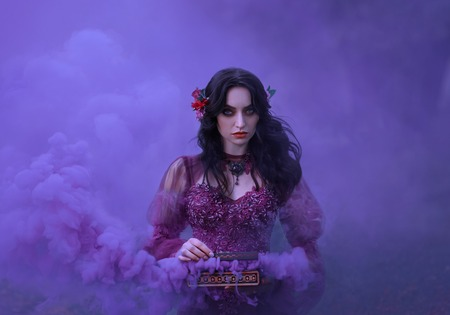 Pandoras box The treacherous brunette girl in a luxurious dress is holding an open casket in her hands, from which the evils of humanity fly out. Violet smoke with beautiful clouds fills the background. Art photo Фото со стока