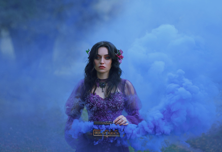 Pandoras box The treacherous brunette girl in a luxurious dress holds an open casket in her hands and stares intently into the camera with blue eyes. cool smoke in beautiful clouds fills the background. Art photo