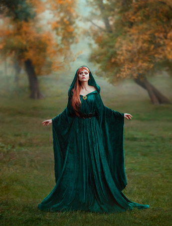 runaway princess with red blond long hair dressed in a green emerald expensive velvet royal cloak-dress with a precious brooch, the girl got lost in a dark foggy forest, fell into a trap, art photo Фото со стока