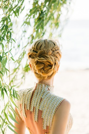 Blond blond hair is professionally made with braids in a magnificent hairstyle for a summer wedding image of a bride or graduate, gentle and neat creative work, light background