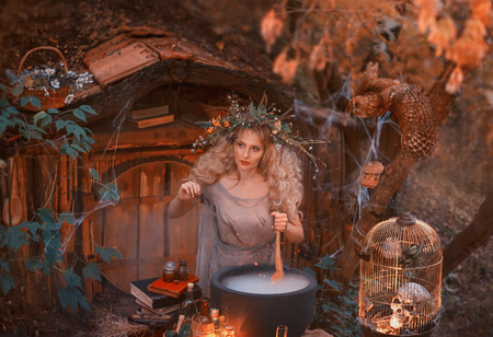 Attractive young girl with blond hair with an amazing lush wreath on her head in the forest is preparing a large cauldron. atmospheric autumn art photo processing in cool orange and green warm colors Stock fotó