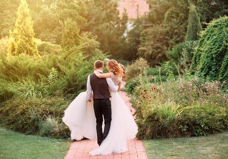 jeune marié en costume porte dans les bras sa fiancée, vêtue d'une longue et magnifique robe blanche luxueuse, marchant dans un magnifique jardin. pas de visages. photo prise de dos. belle photo romantique