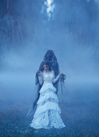 young girl in a white vintage dress and a silver necklace is standing on frozen grass in a thick blue mist in Death captivity and looking down. creative chill color. art photo processing,